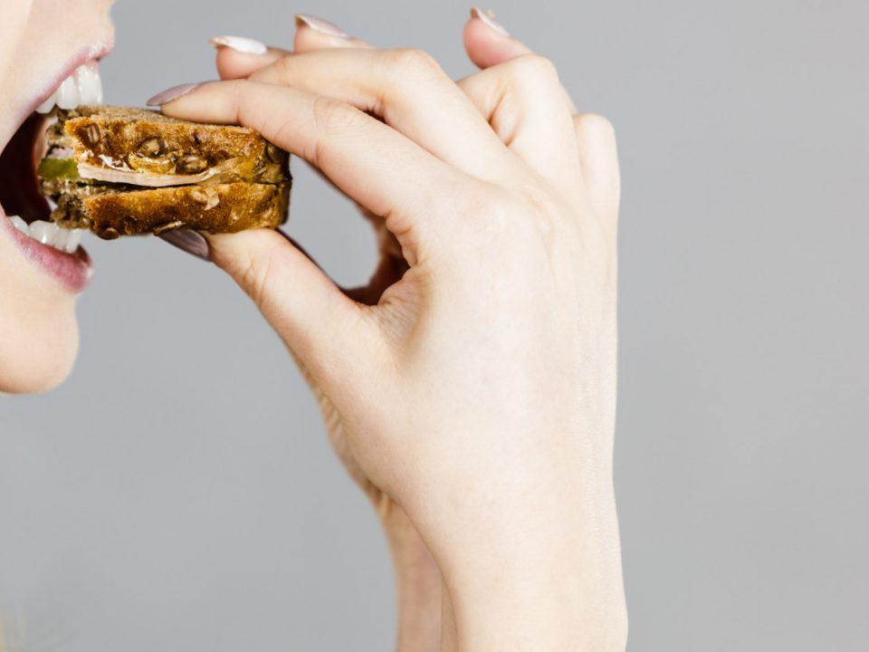 Mulher comendo um sanduíche