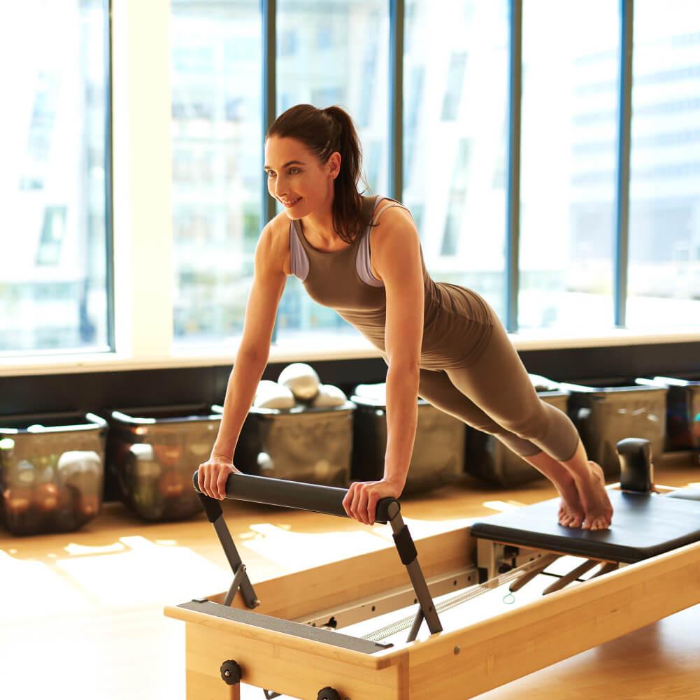Mulher realizando exercício em aparelho de Pilates